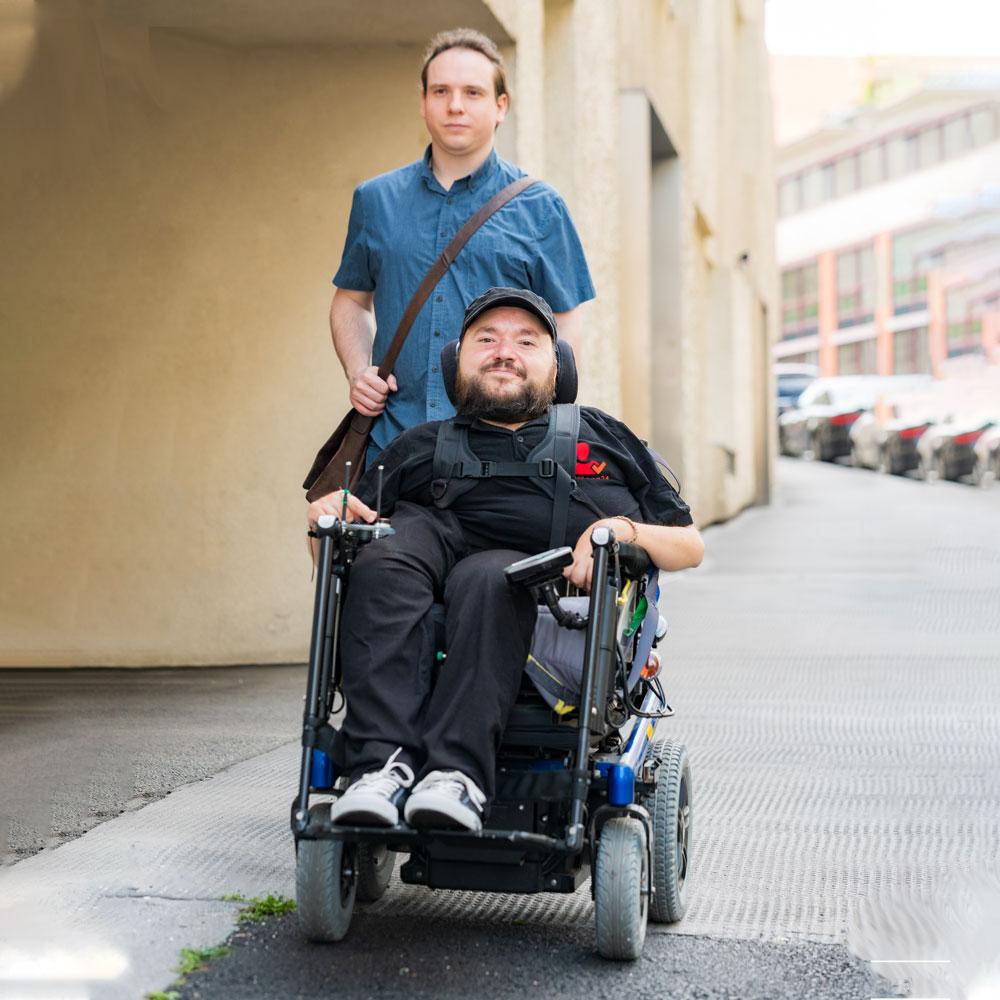 Mann steht hinter Mann im Rollstuhl