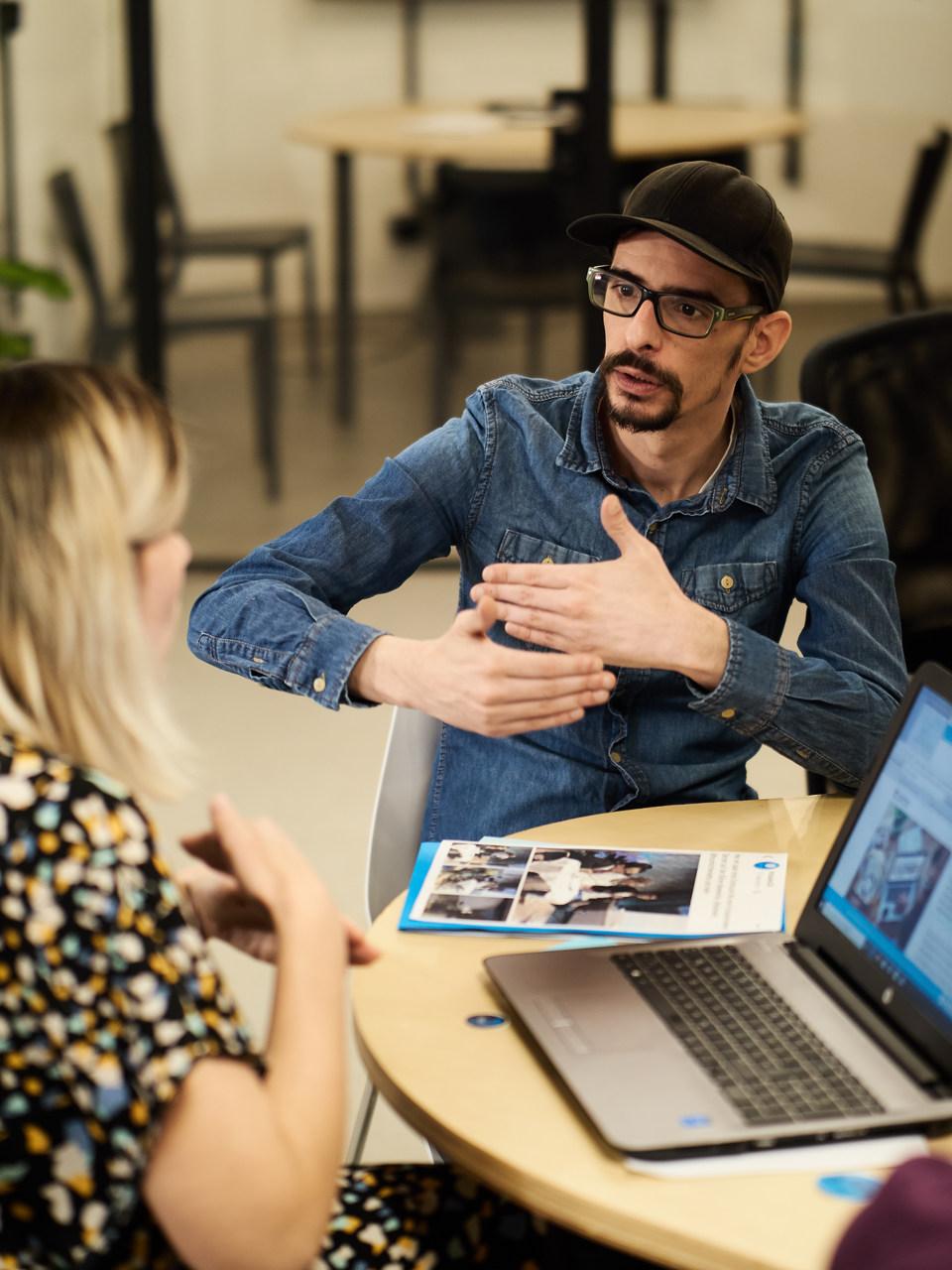 Mann und Frau im Büro sprechen in Gebärdensprache