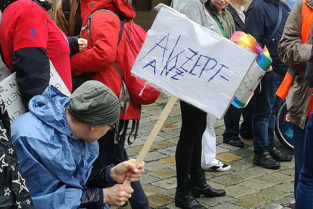 Mann mit Schild mit Aufschrift Akzeptanz