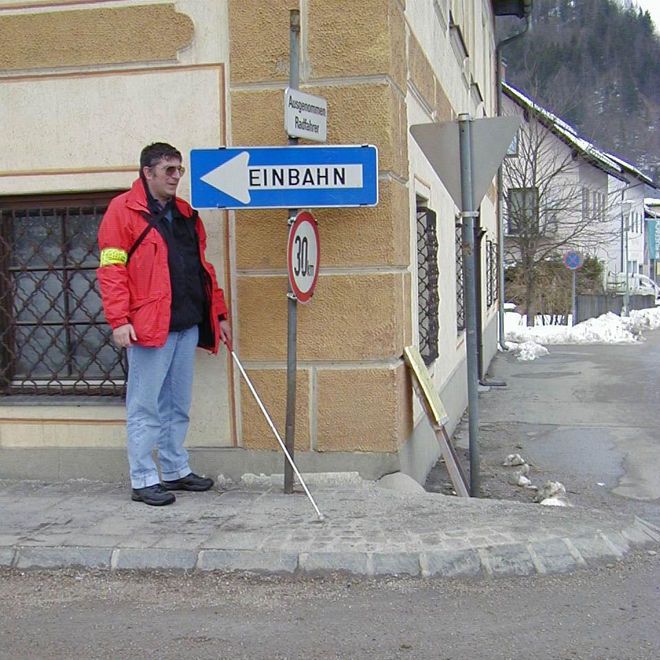 Blinder Mann neben Einbahn-Schild